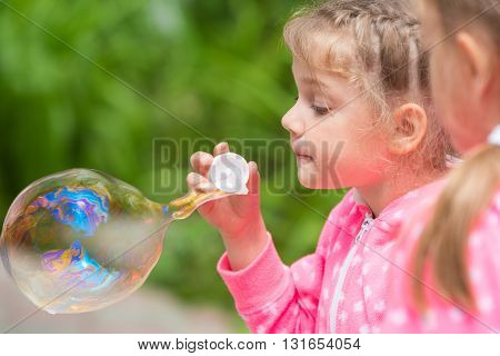 Five-year Girl Inflates A Large Bubble, Another Girl With Interest Looks At Her