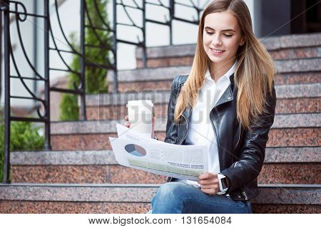 Modernity.  Smiling and cheerful young woman reading some articles in a newspaper and drinking coffee while sitting on the stairs