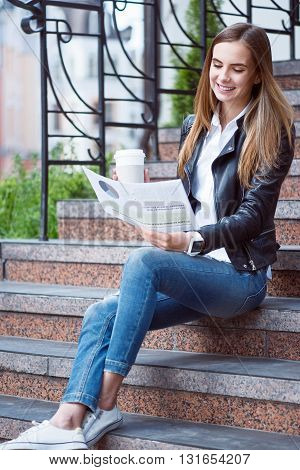 My lifestyle.  Happy and cheerful young woman reading some articles in a newspaper and drinking coffee while sitting on the stairs