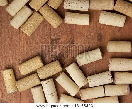 Many wine corks on a dark brown wooden background texture with copyspace