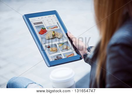 Screen.  Content young woman using a digital tablet and looking some photos there while drinking coffee