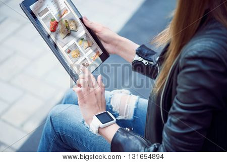 Calories.  A young woman using a digital tablet and looking some photos there and thinking what she is going to cook today