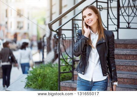 Talking with friend.  Smiling and cheerful woman speaking per cell phone and holding a digital tablet while being in a big city and standing near stairs