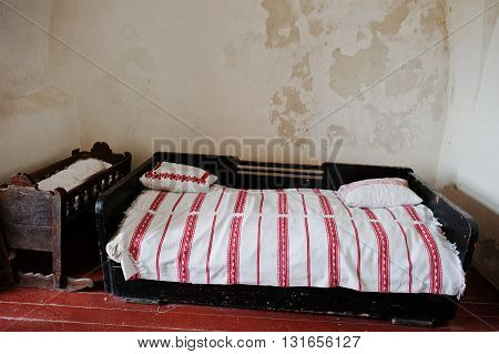 Old Wooden Bed With Child Cradle Background Ragged Wall