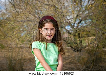 A cute girl sits outside amongst desert trees. She is wearing a large headband and is missing one of her front teeth.