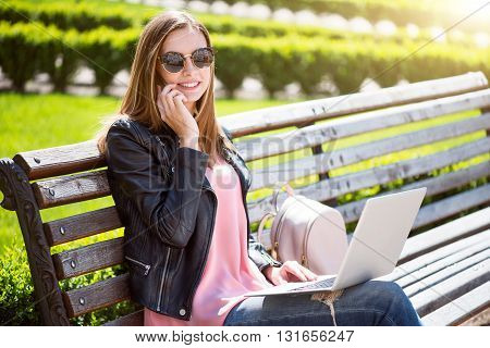 Always in touch.  Cheerful and glad young woman  speaking per sell phone and using a laptop while sitting on a bench and being in a park