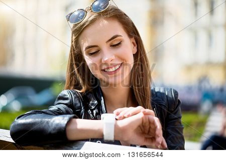 Per phone. Smiling and positive young woman speaking per cell phone with her best friend while sitting on a bench and being in a park