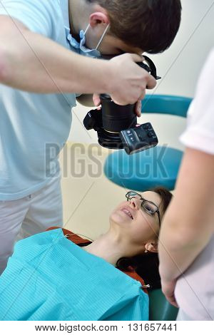 Dentist With Camera Shooting Of Patients