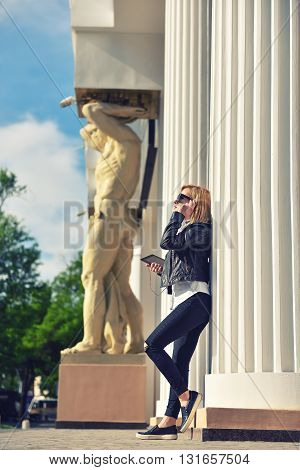 hipster girl with tablet standing near column and listening to music