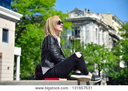 young hipster girl sitting on roof with red book