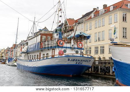 Copenhagen Denmark - July 27 2015: Nyhavn district is one of the most famous landmark in Copenhagen. Ships anchored along the pier.