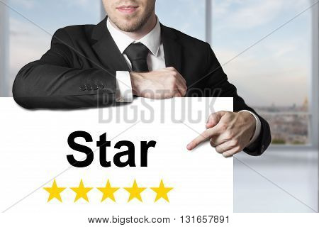businessman in black suit pointing on white sign star golden rating