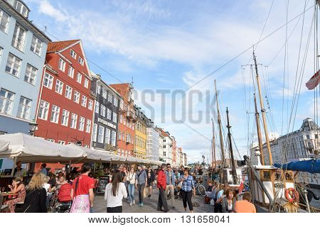 Copenhagen Denmark - July 27 2015: Nyhavn district is one of the most famous landmark in Copenhagen. People enjoy sunny weather in open cafes in Copenhagen.