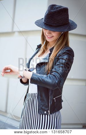 Time to enjoy music.  Cheerful and smiling modern young woman using her cell phone while listening to music and looking at her smart watch