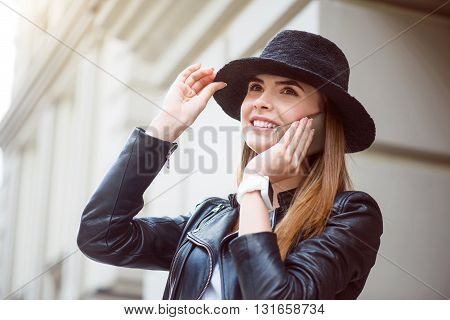 Stylish woman.  Positive and merry modern young woman calling somebody and being in a very good mood