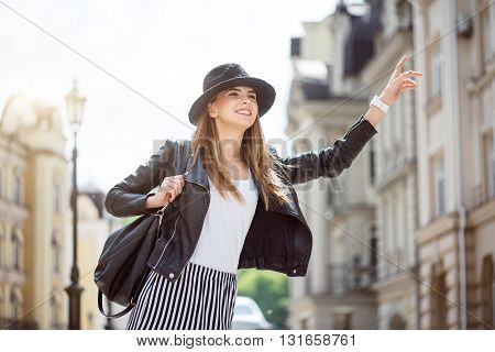 Taxi.  Smiling and very cheerful modern young woman hailing a taxi being in a big city