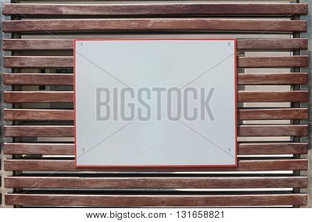 Empty white placard sign board on wooden gate. white placard board on wooden gate. You can write your information text on empty signboard.