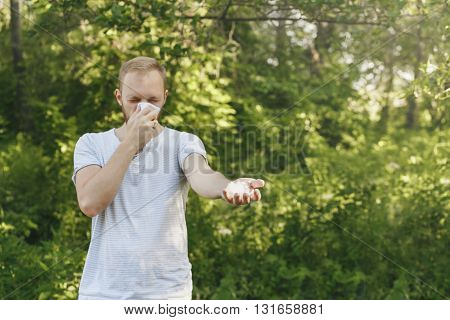 young man suffering spring pollen allergy. Sneezing into a white handkerchief, holding a sprig with fuzz.