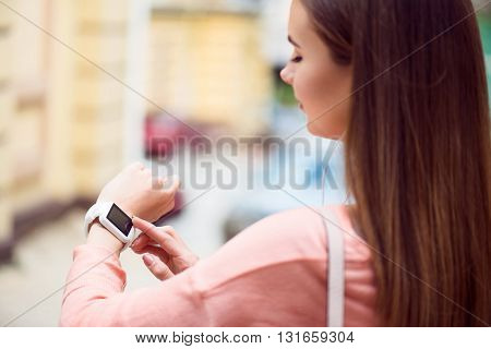 My smart watch. Cheerful and confident modern young woman using her smart watch while listening to music and being outside