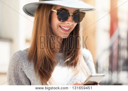 Sms.  Cheerful and content modern young woman using her mobile phone and sending messages while being outside