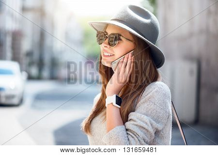 I just call to say.  Smiling and positive modern young woman using her mobile phone and speaking per it while being outside