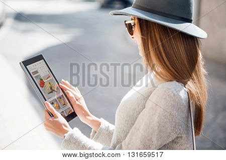 Touching a screen.  Cheerful and positive young woman using a digital tablet and looking some photos there