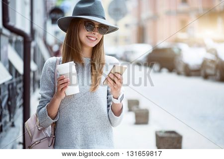 Messaging.  Cheerful and positive modern young woman using her cell phone and writing sms while drinking nice coffee and being outside