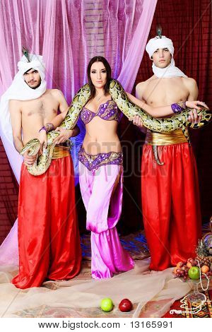 Shot of young people in oriental costumes posing with a python.