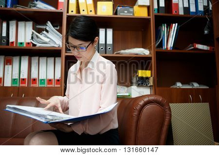 Young woman reading some documents