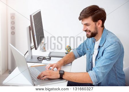 When work is a pleasure. Young smiling man tapping on his laptop while sitting at the table