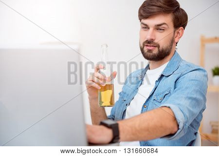 I almost finishing. Handsome bearded man using his laptop and looking at the screen while drinking a beverage