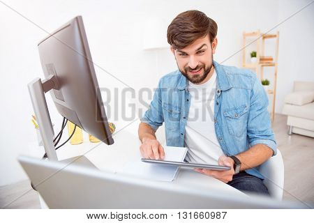 Look here. Cheerful bearded man looking at the screen of his laptop while sitting at the table and holding a tablet in his hands