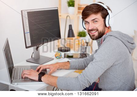 Hey there. Confident young guy looking at the camera while using the laptop with headset