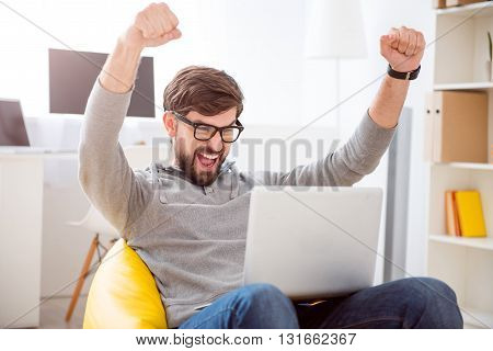 It is a victory. Lively young man looking at the screen while sitting on the armchair and raising his hands above the head