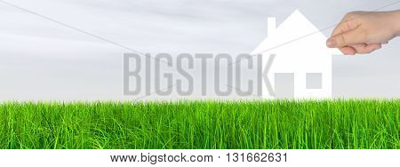 Concept or conceptual white paper house held in hand by a man in a green summer grass over a gray sky background with clouds banner