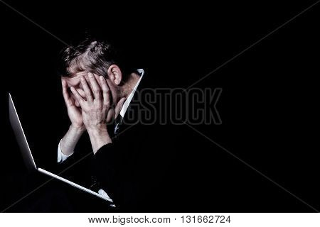 Side view of stressed business man holding his head with laptop in front of him. Dark background with light on subject.