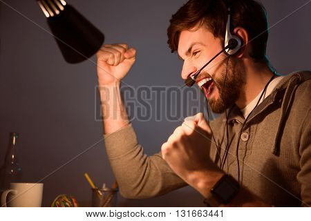 That is amazing. Excited man smiling and doing a sign of victory with hands while using headset