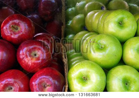 Green and red apples stacked for market