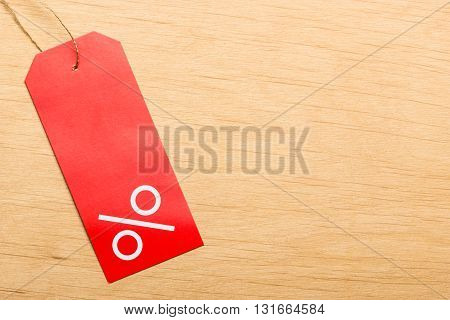 Shopping and sale concept. Red price label with percent sign on wooden surface background. Copyspace
