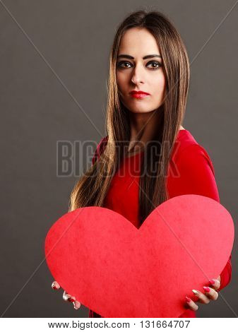 Valentines day concept. Brunette long hair young woman in red dress holding big heart love symbol dark gray background