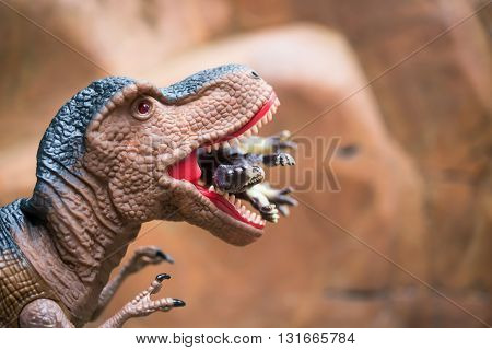 gigantic tyrannosaurus catches a smaller dinosaur in front of a rock mountain