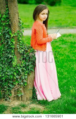 Girl In Dress With Notebook And Pen Near Tree