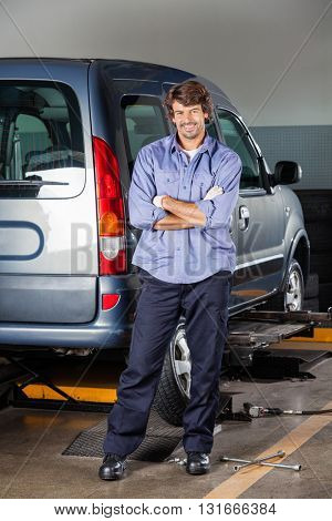 Portrait Of Mechanic Standing By Car At Garage