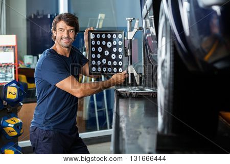 Smiling Mechanic Adjusting Wheel Aligner On Car