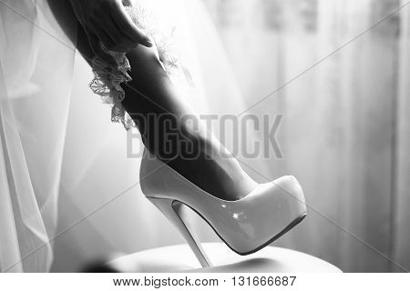 Sexy female bridal leg in beautiful wedding ribbon garter and glamour shiny leather shoes on high heel black and white