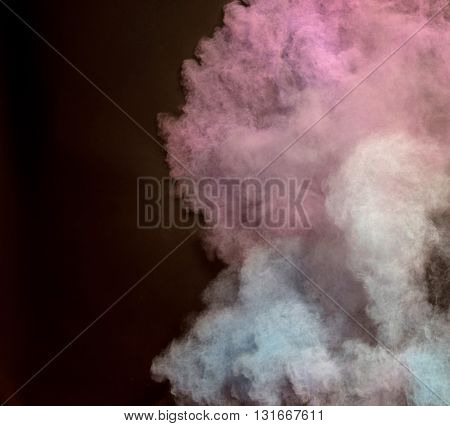 Enticing and gorgeous powder of colors being spread in air at night. The shot with powder of blue and pink colors look really amazing. On the background, black night view is seen.