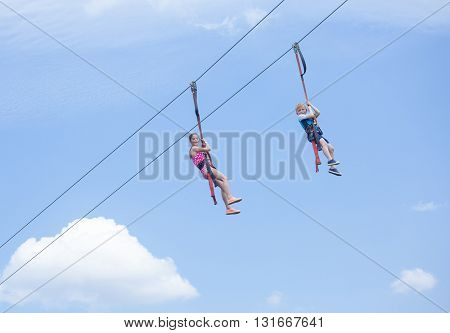 Two happy kids playing on a zip line view from below