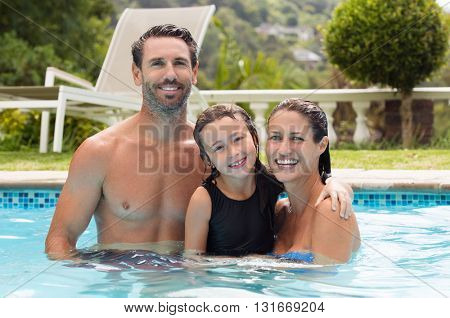 Family having fun in swimming pool. Family playing in swimming pool of a private villa. Happy parents with smiling daughter in swimming pool enjoying the summer.