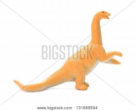 side view orange diplodocus toy on a white background