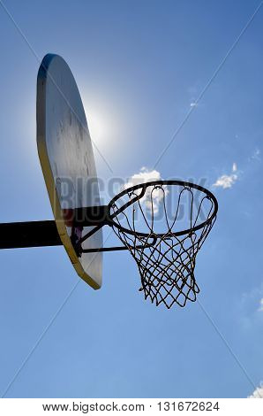 The sun is partially blocked by a backboard of a basketball standard.